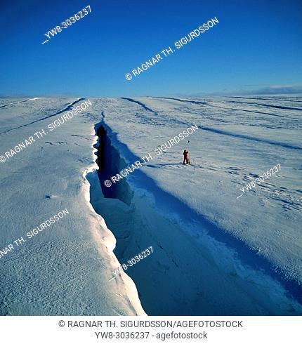 Scientist taking measurements by a large crevasse, Sidujokull, Vatnajokull Ice Cap, Iceland
