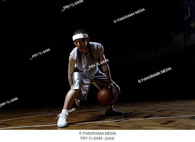 Basketball player dribbling ball on court