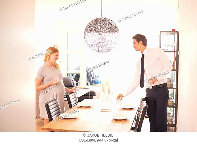 Pregnant couple laying dining table