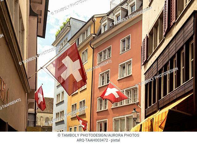 Detail of picturesque old town street with Swiss flags and residential buildings, Zurich, Switzerland