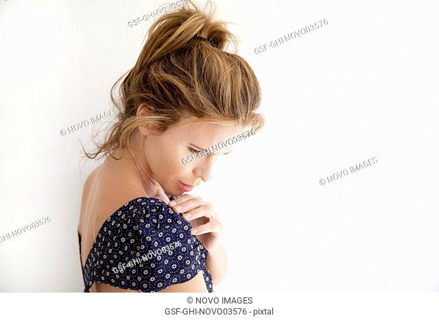 Head and Shoulders Portrait of Contemplative Mid-Adult Woman in Cap Sleeve Dress Looking Down, White Background
