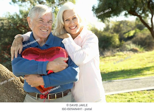Wife hugging husband with red heart-shaped balloon, Hahn Park, Los Angeles, California, USA