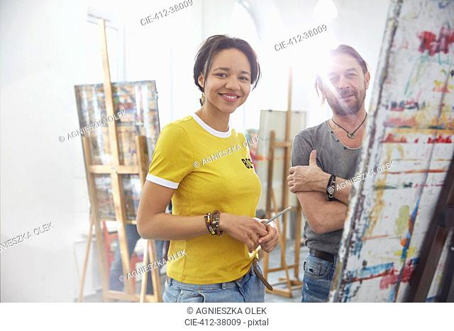 Portrait smiling artists painting at easel in art class studio