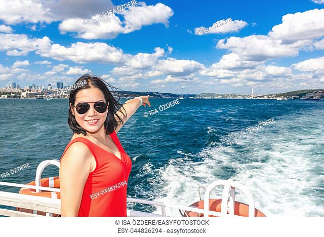 Beautiful Chinese woman shows First Bridge while cruising with ferry in Istanbul, Turkey