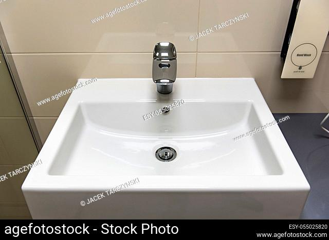 Classic modern white washbasins with chrome water tap and soap holder