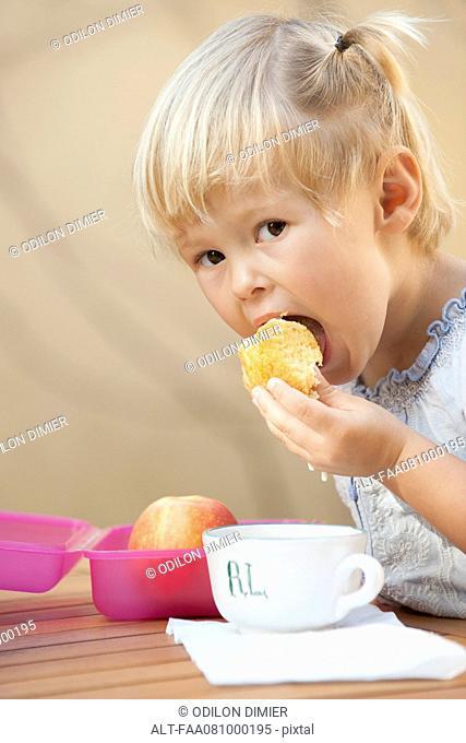 Little girl eating a snack