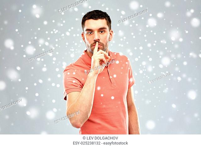 silence, gesture, winter, christmas and people concept - serious young man making hush sign over snow on gray background