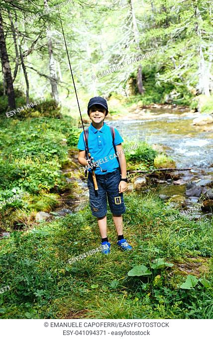 boy child fishing in the river in the mountains in the alps in the summer