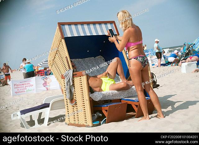 Poland, Jurata 16.08.2015. Woman takes picture of a man on the beach in the famous luxury resort on the Hel peninsula. Photo CTK/Grzegorz Klatka