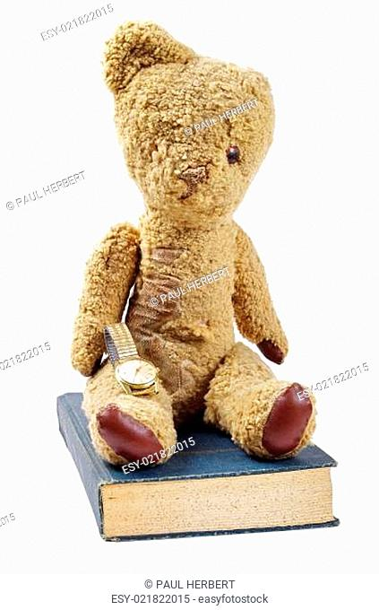 antique teddy bear with watch and old book