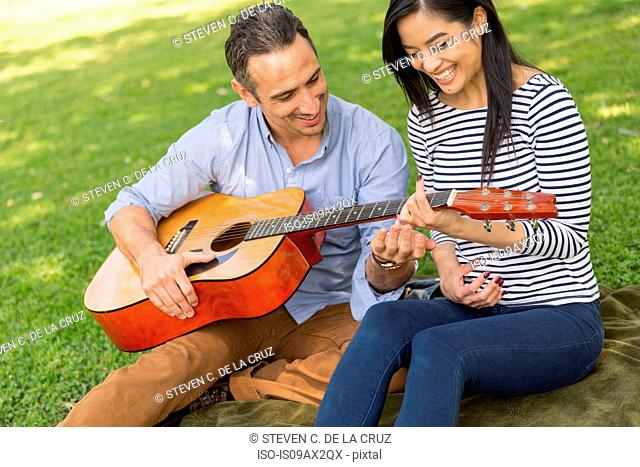 Couple sitting on grass playing acoustic guitar smiling