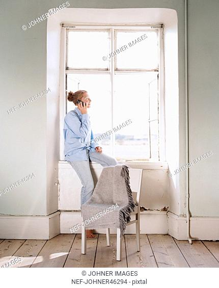 Young woman looking through window while talking via cell phone
