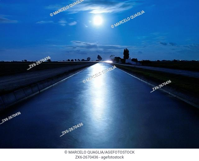 Full moon reflecting over main irrigation channel. Ebro River Delta Natural Park. Tarragona province, Catalonia, Spain