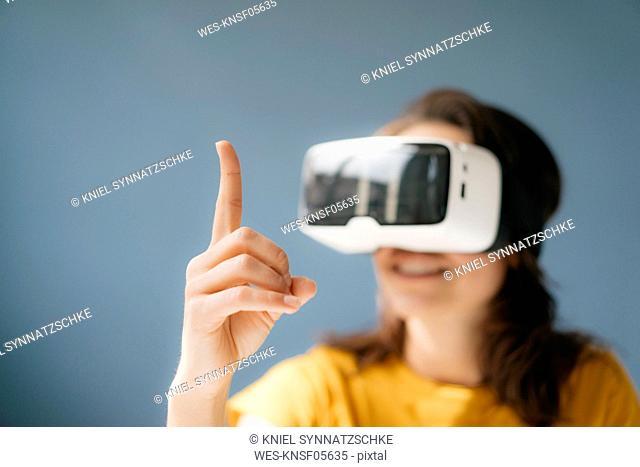 Woman wearing VR glasses, watching raised finger