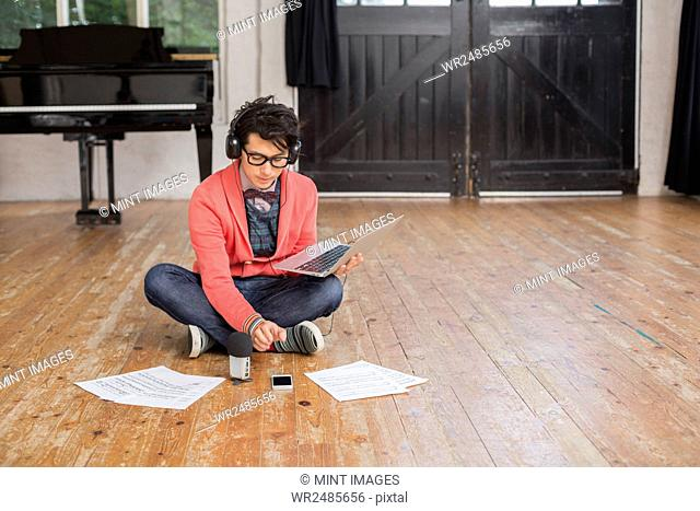 Young man sitting on the floor in a rehearsal studio, using a laptop computer, looking at sheet music
