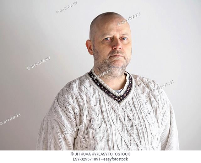 Portrait, casual looking caucasian male wearing a white pullover, he looks toward the camera, copy space is on the left