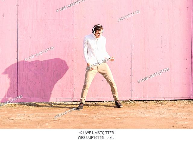 Exuberant young man listening to music in front of pink wall