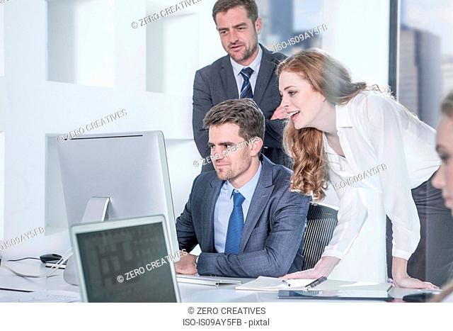 Businessmen and businesswoman using computer in office