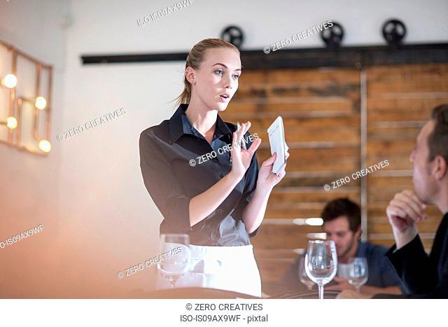 Waitress explaining to customer in restaurant