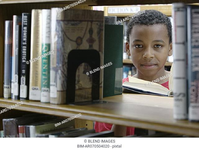 Portrait of boy looking at books in library