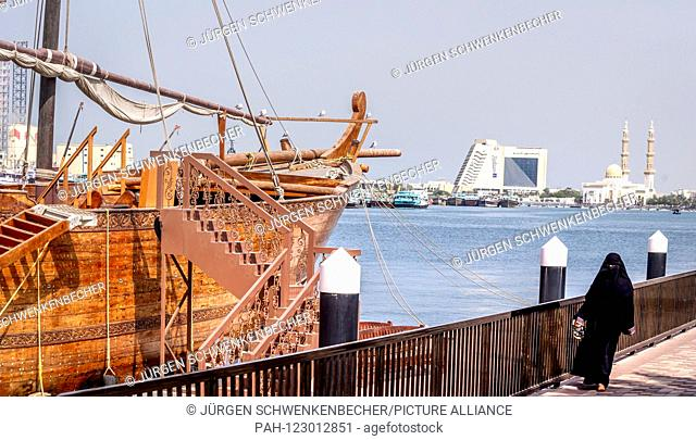 A veiled woman walks past the Creek in downtown Sharjah on a large dhow. The dhow is waiting for tourists. In the background you can see a hotel (Radisson Blu...