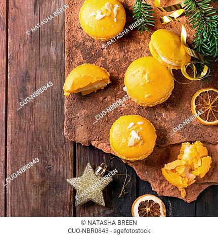 Whole and broken orange lemon homemade macaroons with white chocolate and citrus sugar and zest on old clay board over dark wooden background with Christmas...