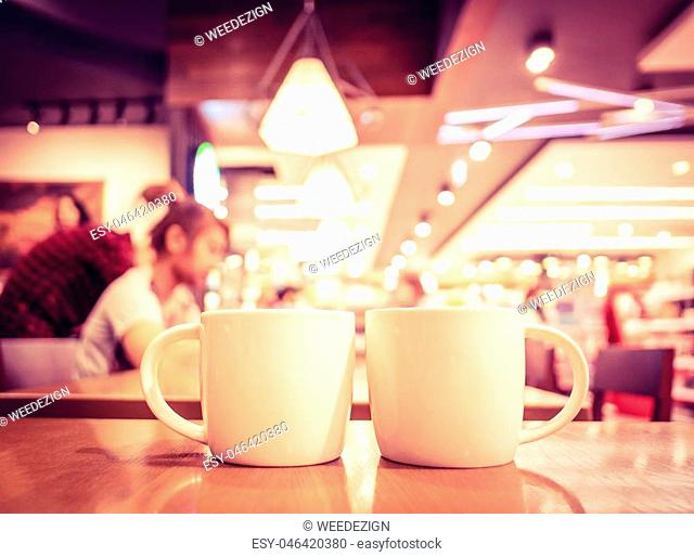 Vintage filter, couple of White coffee cup on wood table with blurred cafe bokeh light background