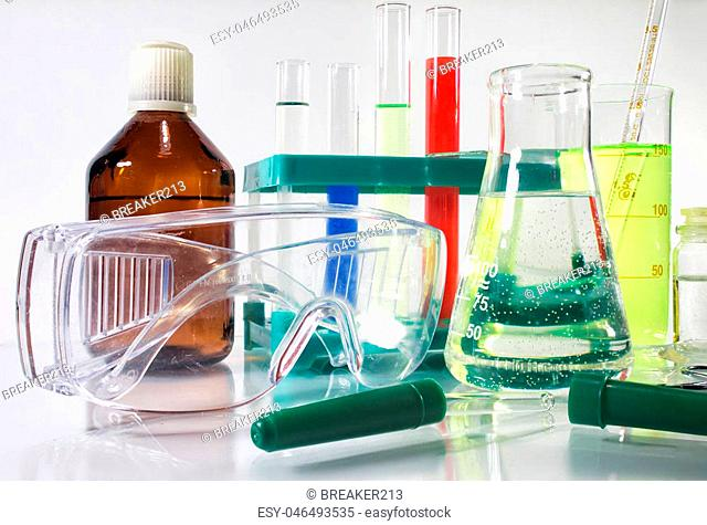 Photo composition of a laboratory bottles, test-tubes, protective glasses & medicine dropper laying on a white glass table