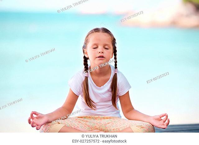 Child doing meditating exercise on wooden platform sea shore outdoors. Healthy lifestyle. Yoga girl