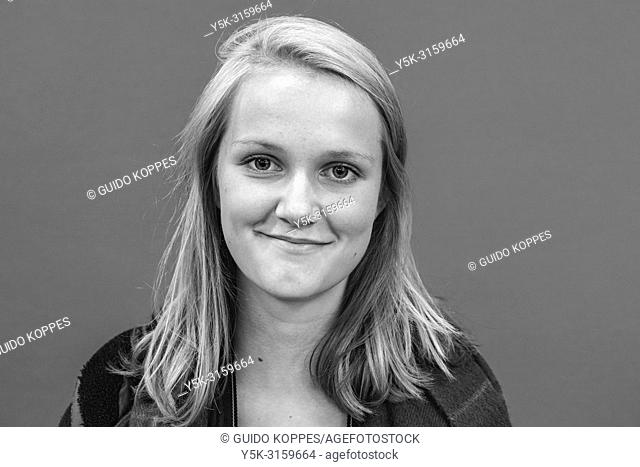 Tilburg, Netherlands. Portrait of a blonde, female student against a green background or green-screen. Black & White image