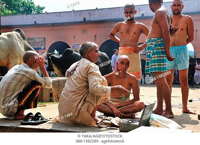 Pilgrims shaving hair at the ghat by the Ganges river