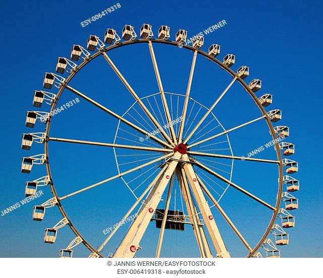 Sunlit ferris wheel on a summer day