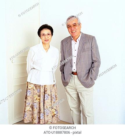 Portrait of a Senior Couple Standing In Front of a White door, Looking at Camera, Smiling, Front View