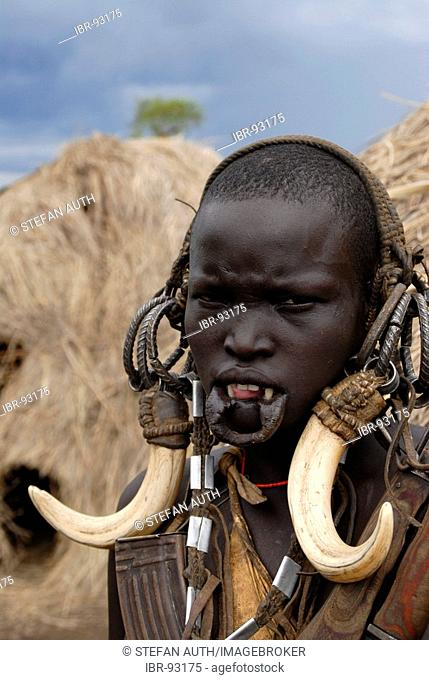 Portrait woman of the Mursi people wearing head decoration of animal teeth in front of her hut Ethiopia