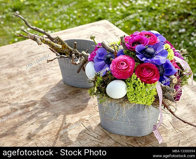 Easter bouquet of ranunculus and blue anemone with Easter eggs in a zinc flower pot on an outdoor wooden table