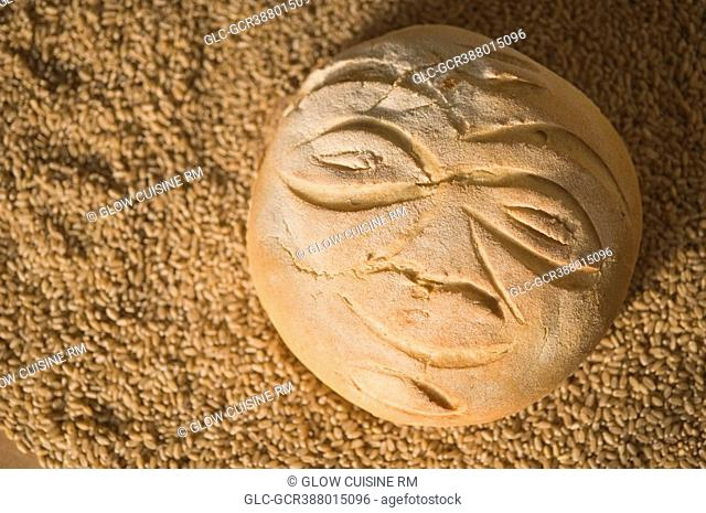 Close-up of anthropomorphic face on a loaf of bread with wheat