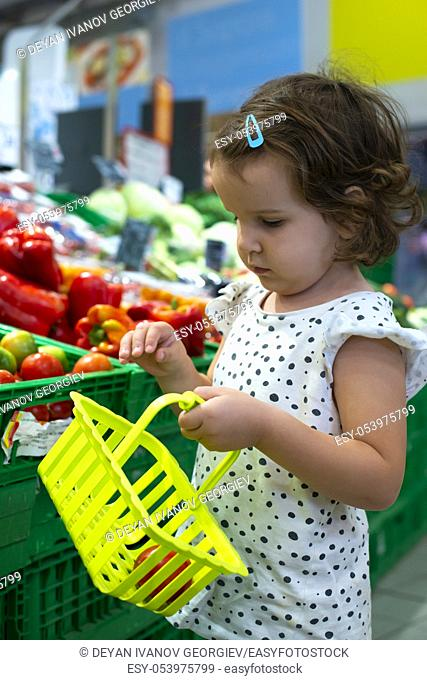 Little girl buying tomatoes in supermarket. Child hold small basket in supermarket and select vegetables. Concept for healthy eating for children