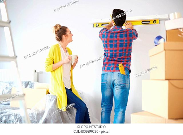 Young couple at home, surrounded by cardboard boxes, man checking shelf with spirit level