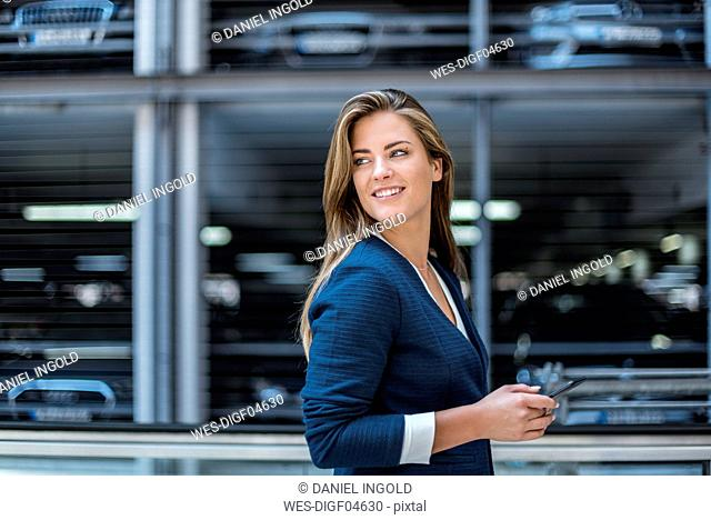 Portrait of smiling young businesswoman with cell phone in front of blurred parking garage