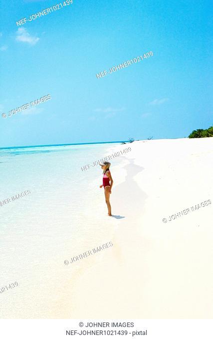 Girl standing on edge of beach