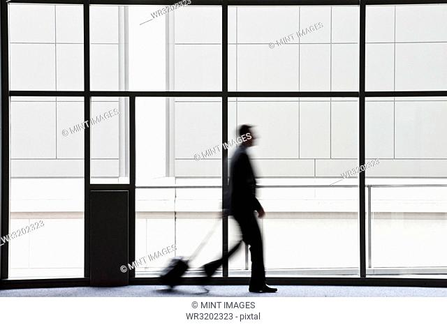 A businessman blurred in silhouette while walking past a large window in a convention centre lobby