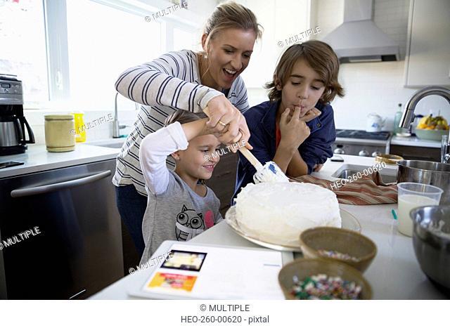 Family baking cake in kitchen