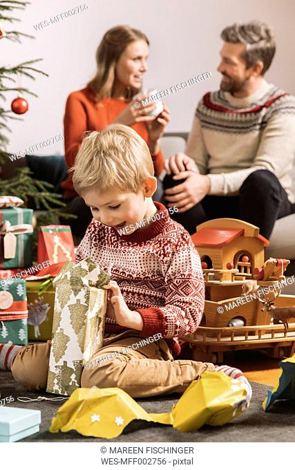 Little boy happily looking at Christmas gift with parents in background