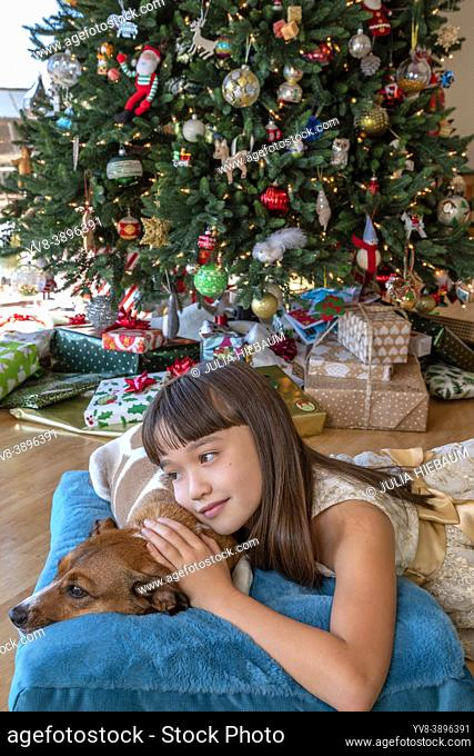 Eight year old girl laying with her dog in front of the Christmas tree