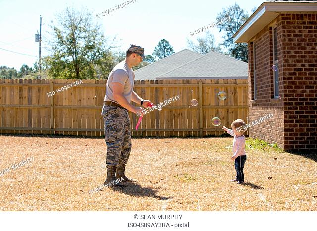 Young male soldier blowing bubbles with toddler daughter in garden at air force military base