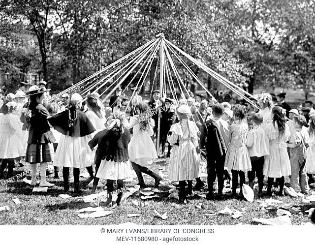 Children dancing around a May pole, Central Park, New York City, USA