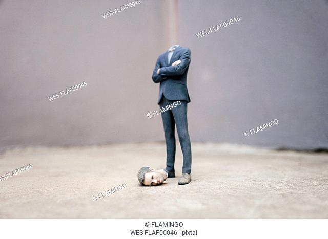 Headless businessman figurine standing on cocrete