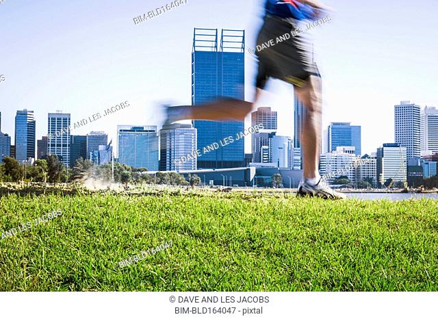 Blurred view of Caucasian man running on grassy hill near Perth city skyline, Western Australia, Australia
