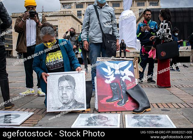 A close relative places a drawing of Oscar Alexander a young male killed during the commemoration of the international day of the victims of force disappearance...