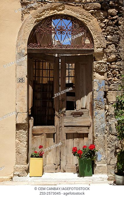 Flower pots in front of an antique house door in the old town, Rethymno, Crete, Greek Islands, Greece, Europe
